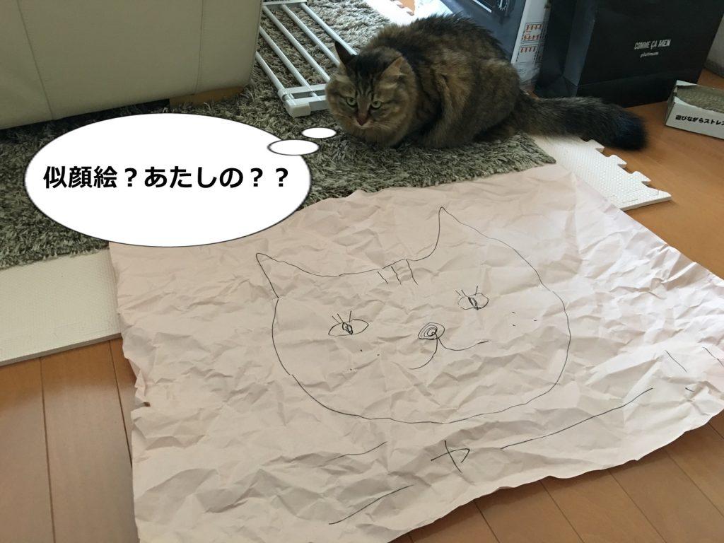 自分の似顔絵を見る猫